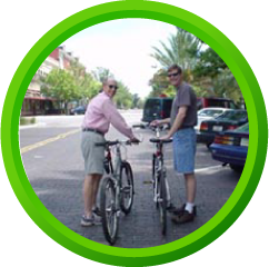 Two men standing on a roadway with their bikes and Spiderflex hornless saddles