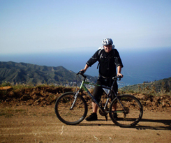 Kyle and his Mountain bike with Spiderflex hornless saddle on a scenic road - was ready to take up a new hobby but is painfree cycling now - Kyle