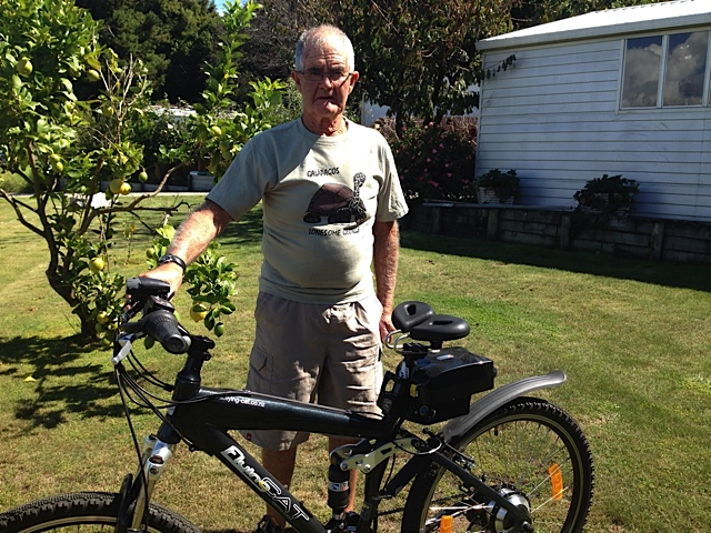 Frank from New Zealand standing with his Flying Cat e mountain bike with Spiderflex seat installed comments on comfort