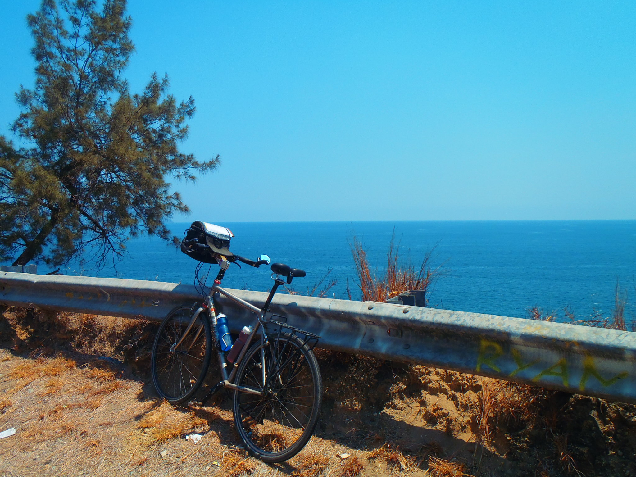 Henry-Tour D'Afrique-Bicycle along guard rail overlooking water