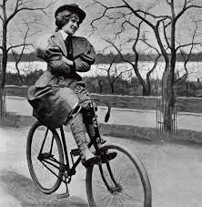 Black and white photo of proper woman on an old bicycle